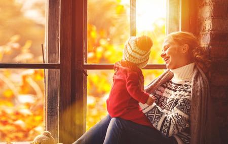 mama e hijo: madre de familia feliz y bebé que juega y se ríe de la ventana en el otoño