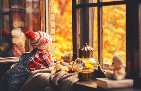 child girl looking through the open window at the beautiful nature autumn gold Stock Photo