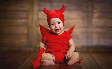 funny baby in devil halloween costume with horns on a dark wooden background Stock Photo