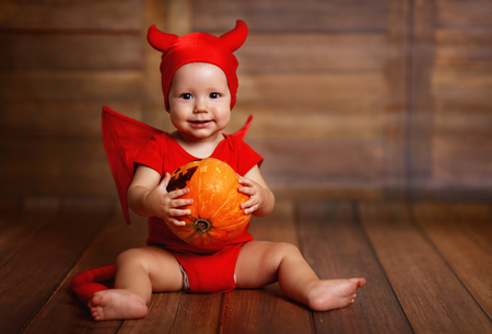 unruly: funny baby in devil halloween costume with pumpkin on a dark wooden background Stock Photo