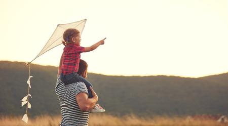 silueta niño: feliz padre de familia y el niño en prado con una cometa en el verano en la naturaleza