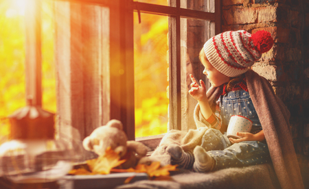 child girl with cup tea looking through the window at the beautiful nature autumn gold Stock Photo