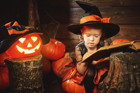 child little witch with pumpkin Jack and magical book of spells in the old hut