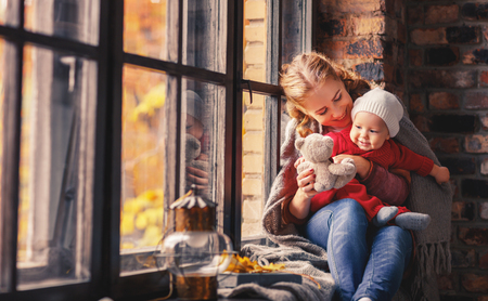 happy family mother and baby playing and laughing at the window in the fall
