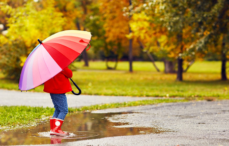 happy child girl with umbrella walking through the puddles after autumn rain Stockfoto