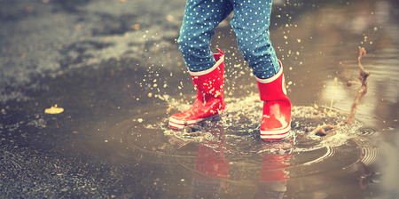 legs of child in red rubber boots jumping in the autumn puddles Banco de Imagens