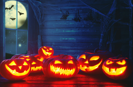 spooky halloween background. scary pumpkin with burning eyes and smiles in the night