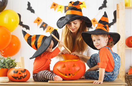 making a face: Happy family of mother and children prepare for Halloween pumpkins decorate the home