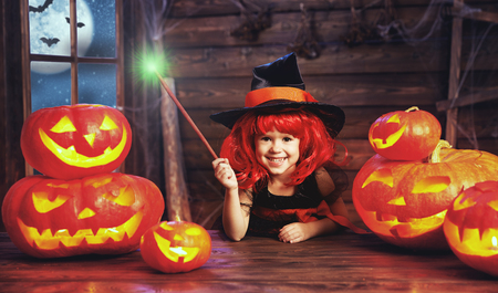 wood spider: Halloween. child little witch with magic wand and pumpkin Jack   in old hut