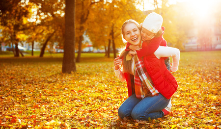 happy family nature: happy family: mother and child little daughter play cuddling on autumn walk in nature outdoors