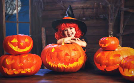 Víspera de Todos los Santos. pequeña bruja niño con calabaza de la linterna de Jack en la vieja cabaña Foto de archivo