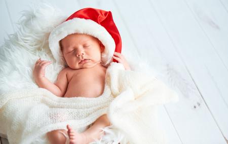 recien nacidos: bebé recién nacido durmiente en una tapa de Santa Navidad Foto de archivo