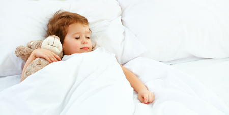 child little girl sleeps in the bed with a toy teddy bear Foto de archivo