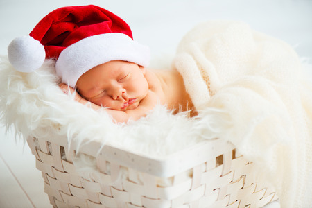 sleeper newborn baby in a Christmas Santa cap