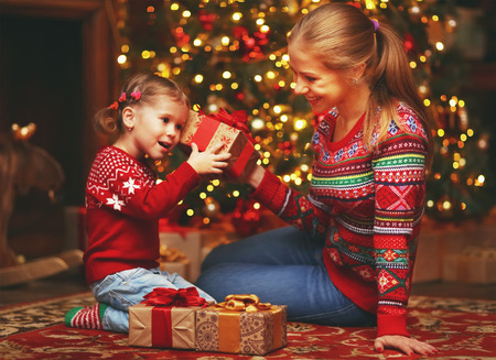 Happy family mother and child girl near a Christmas tree with Christmas present Stock Photo