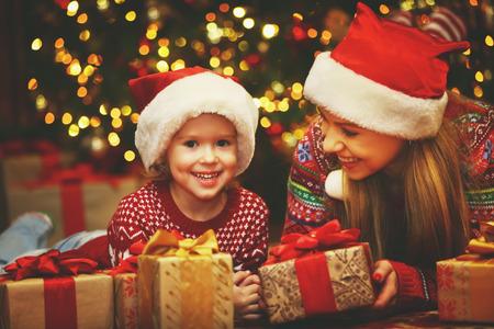 christmas tree presents: Happy family mother and child girl near a Christmas tree with Christmas present Stock Photo