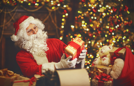 Santa Claus at desk with letters, toys, gifts near Christmas tree