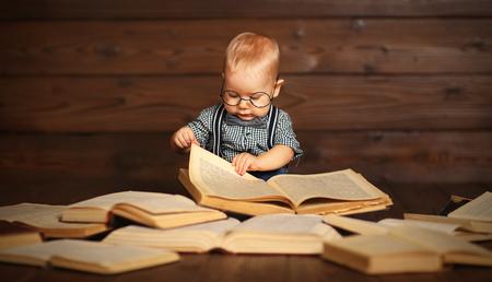 Grappige baby met boeken in glazen op een houten achtergrond Stockfoto