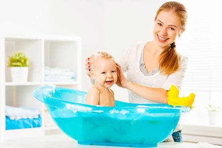 행복 한 가족의 어머니는 파란색 욕조에 아기를 목욕