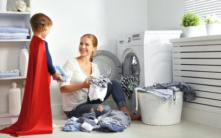 familie moeder en kind meisje kleine superheld helper in wasruimte in de buurt van een wasmachine en een vuile kleren