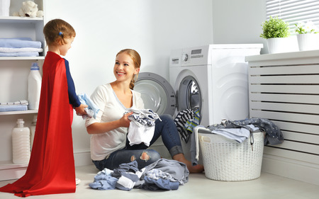 family mother and child girl little superhero helper in laundry room near washing machine and dirty clothes Imagens