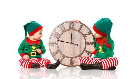 クリスマスのコンセプトです。時計は、白い背景で隔離のサンタの 2 つの小さなエルフ ヘルパー