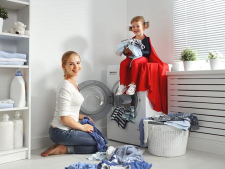 Mère de famille et enfant fille petit assistant de super-héros dans buanderie près de lave-linge et des vêtements sales Banque d'images - 65614628
