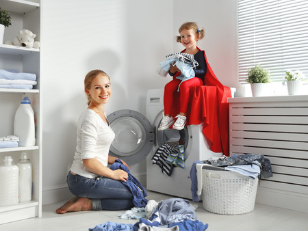 family mother and child girl little superhero helper in laundry room near washing machine and dirty clothes Archivio Fotografico