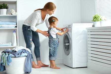 Familie Mutter und Kind Mädchen kleiner Helfer in Waschraum in der Nähe von Waschmaschine und schmutzige Kleidung Standard-Bild - 64792523