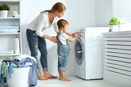 rodina matku a dítě dívka malý pomocník v prádelně v blízkosti pračkou a špinavé prádlo