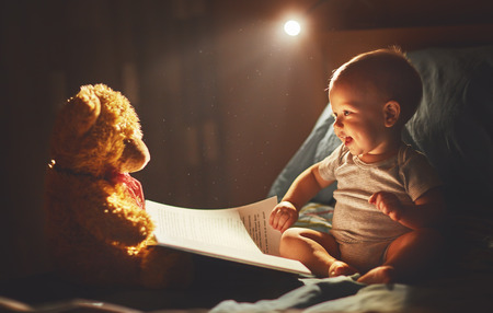 Happy baby reading a book with teddy bear in bed in the dark