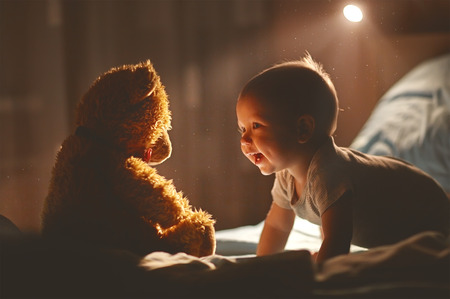 Happy baby laughing with teddy bear in bed in the dark