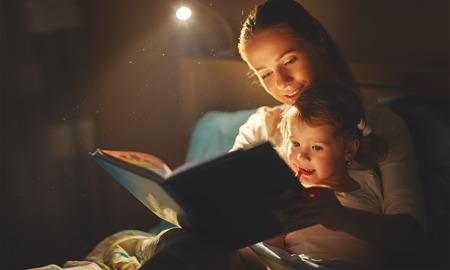 moeder en kind meisje het lezen van een boek in bed voor het slapen gaan Stockfoto