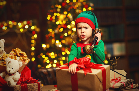 little child: Christmas concept. Little Elf  child  working, talking on the phone