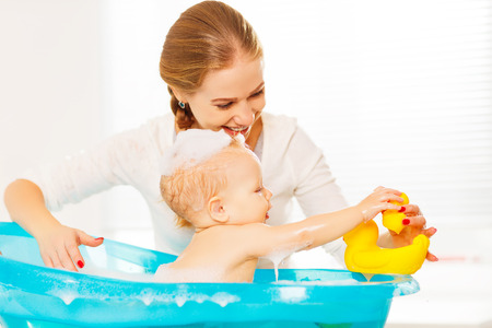 Happy family mother bathes the baby in a blue bath Stock Photo