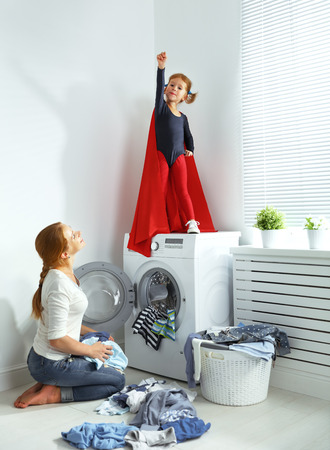 family mother and child girl little superhero helper in laundry room near washing machine and dirty clothes Stock Photo