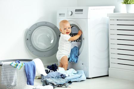 gelukkig baby boy om kleren en lacht wassen in de wasruimte Stockfoto