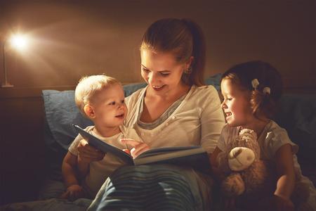 gelukkig gezin moeder en kinderen een boek lezen in bed 's avonds