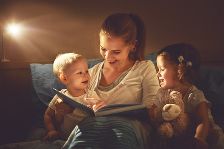 happy family mother and children read a book in bed evening