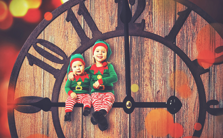two child: Christmas concept. Two little elf helper of Santa on clockwise Stock Photo