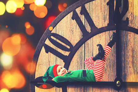 clockwise: Christmas concept. Little Elf child on clockwise Stock Photo