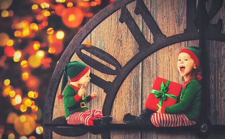 clockwise: Christmas concept. Two little elf helper of Santa on clockwise Stock Photo