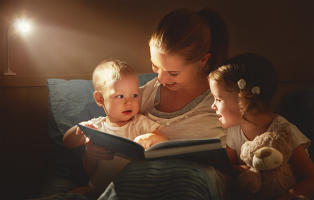 happy family mother and children read a book in bed evening Reklamní fotografie - 65840993