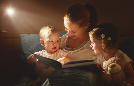 madre de familia feliz y los niños leen un libro en la cama por la noche