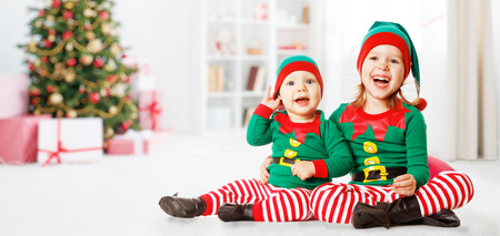 Christmas concept two happy cheerful child in costume an elf at home
