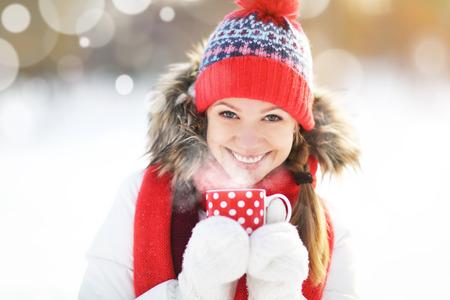 Gelukkige jonge vrouw met een kopje hete thee in de winter wandeling buiten Stockfoto - 65151118