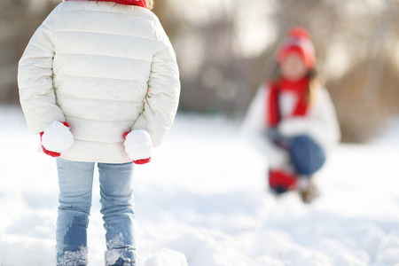 palle di neve: felice madre e figlia famiglia bambino si diverte, giocando a palle di neve alla camminata inverno all'aperto