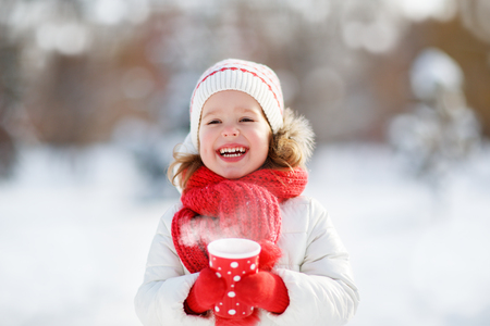 hot drink: Happy child girl with a cup of hot tea in winter  walk outdoors