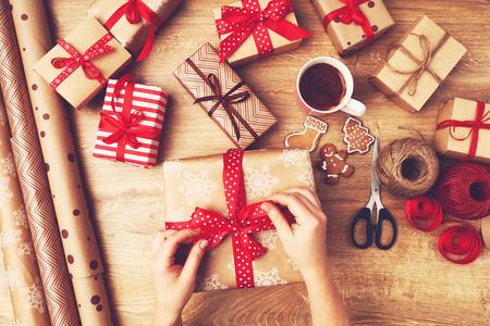 クリスマス プレゼントで女性パック ボックスの手が木製のテーブル プレゼントします。