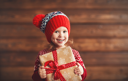 christmas present: happy child girl with a Christmas present on wooden background